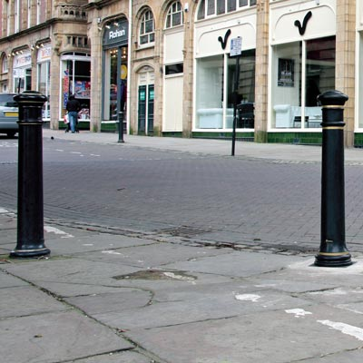 Glasdon Manchester bollard with gold banding (right) sited alongside an existing cast iron bollard (left)